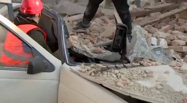 Ráhulló törmelék alól, kocsija roncsaiból szabadítanak ki egy férfit Petrinja városában.